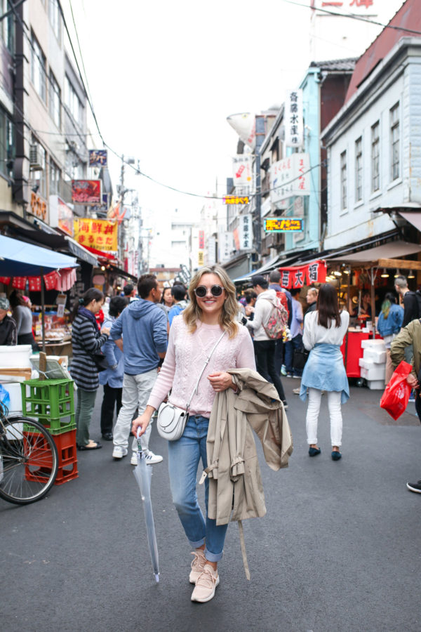 Travel blogger Jessica Sturdy styling a pink J.Crew sweater with Vineyard Vines boyfriend jeans and sneakers while traveling in Japan.