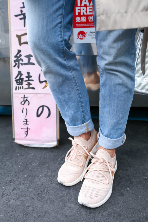 Jessica Sturdy styling blush pink sneakers with cuffed boyfriend jeans at Tsukiji Market in Japan.