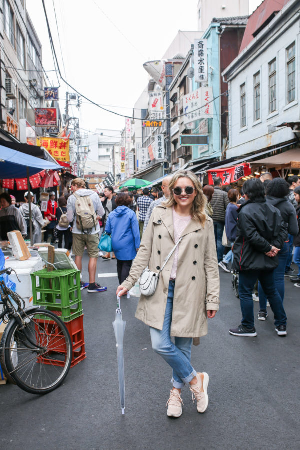 Jessica Sturdy wearing a trench coat, jeans, and sneakers at Tsukiji Fish Market in Tokyo, Japan.