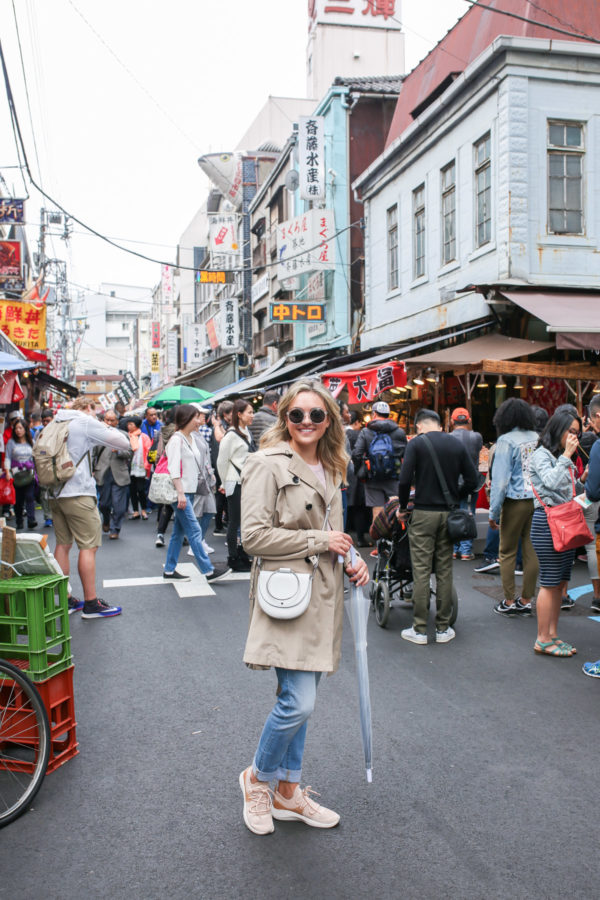 Travel blogger Jessica Sturdy at Tsukiji Market in Tokyo, Japan wearing a tan trench coat, white Theory crossbody ring bag, jeans, sneakers, and a clear umbrella.
