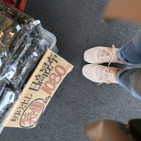 Jessica Sturdy wearing blush pink gym shoes with cuffed boyfriend jeans at Tsukiji Market in Tokyo, Japan.
