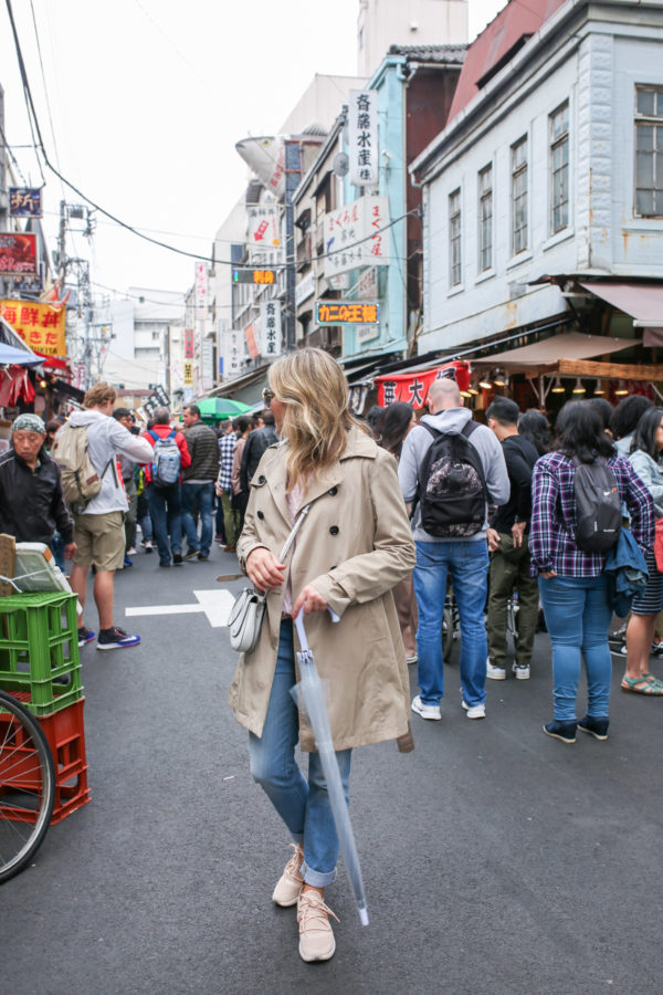 Travel blogger Jessica Sturdy at the Tsukiji Market in Tokyo Japan wearing a trench coat, cuffed jeans, and sneakers with a clear umbrella on a rainy day.