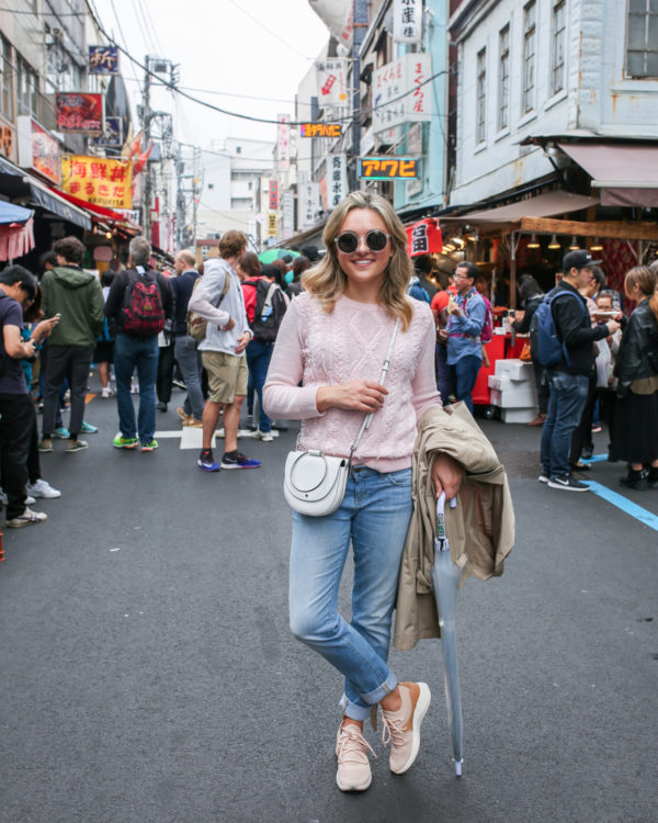 Fashion and lifestyle blogger Jessica Sturdy wearing a pink sweater, boyfriend jeans, and sneakers at Tsukiji Market in Tokyo, Japan.