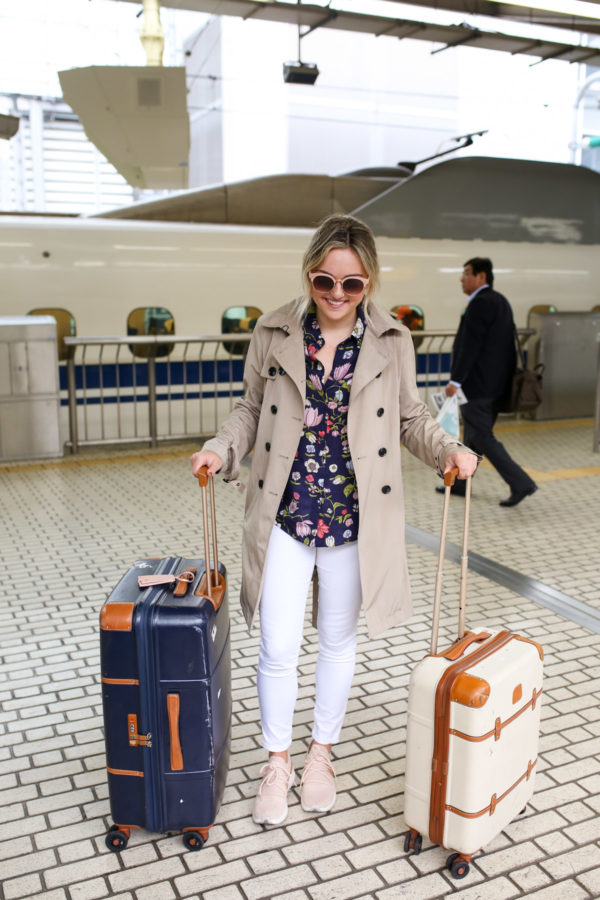 Jessica Sturdy wearing a trench coat and white jeans at train station in Tokyo, Japan.