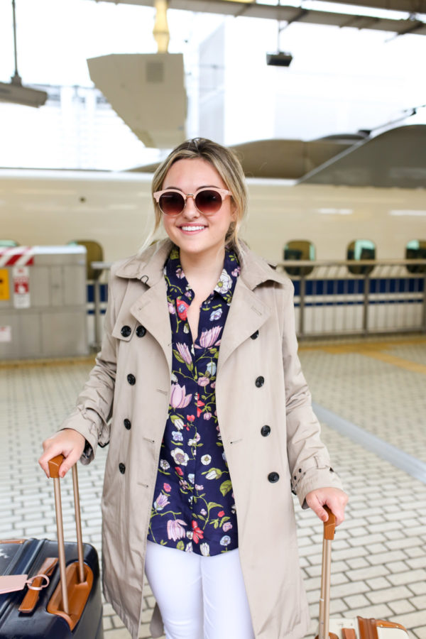 Travel blogger Jessica Sturdy wearing a floral shirt with a camel trench coat in Japan.