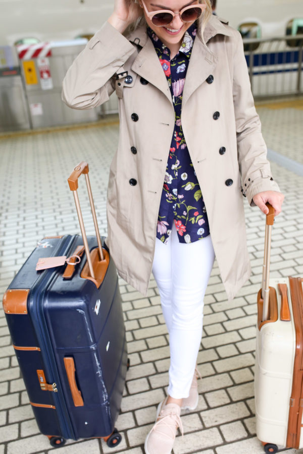 Jessica Sturdy styling a navy floral blouse with white denim, a trench coat, and pink sneakers for a travel day in Japan.