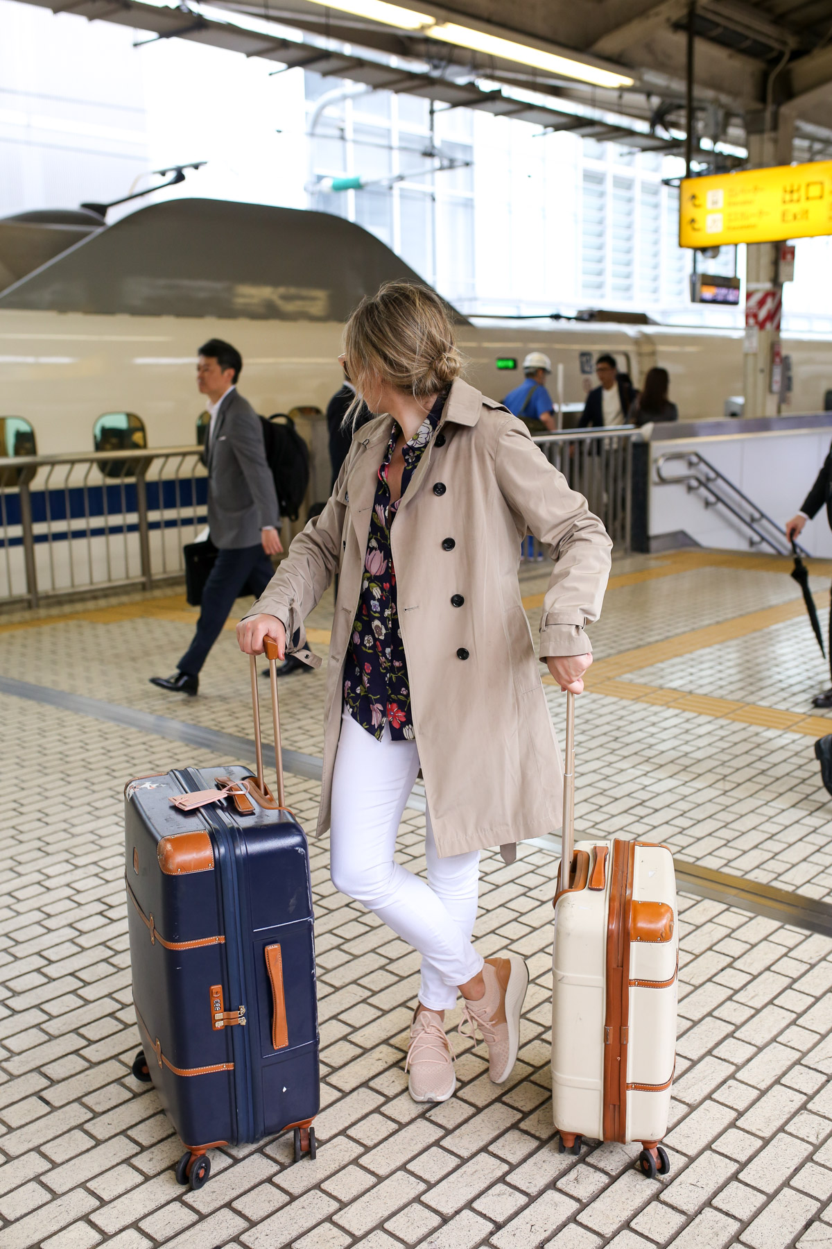 Jessica Sturdy at Tokyo Station wearing a trench coat and white jeans.