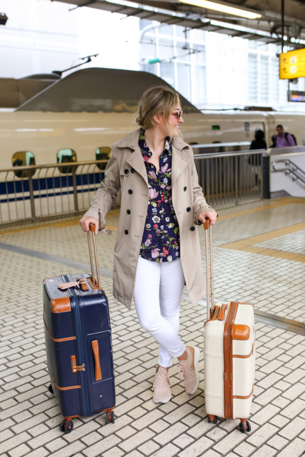 Jessica Sturdy wearing a trench coat, Rebecca Taylor floral blouse, white jeans, and sneakers at Tokyo Station in Japan.