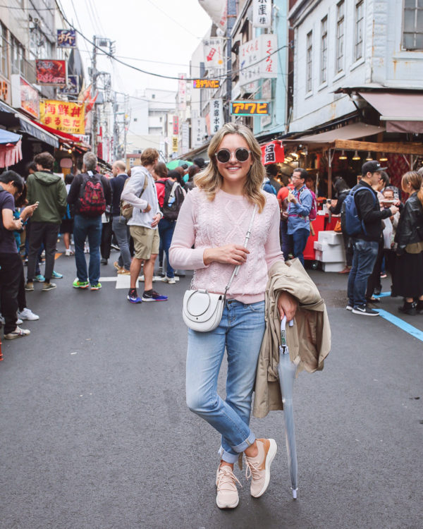 Bows & Sequins Travel Guide in Tokyo Japan. Jessica Sturdy at the Tsukiji Fish Market in Ginza wearing a J.Crew sweater, Vineyard Vines boyfriend jeans, a trench coat, a clear umbrella, a Theory white ring crossbody bag, and blush pink sneakers.