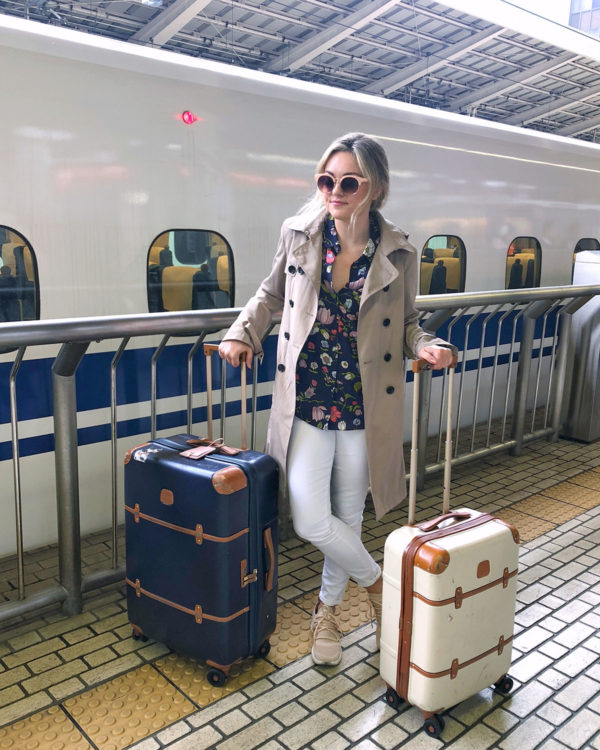 Bows & Sequins Travel Guide in Tokyo Japan. Jessica Sturdy is wearing a trench coat, Rebecca Taylor floral blouse, white jeans, Timberland blush pink sneakers, pink sunglasses, and two Brics Luggage suitcases at the JR Shinkansen platform at Tokyo Station