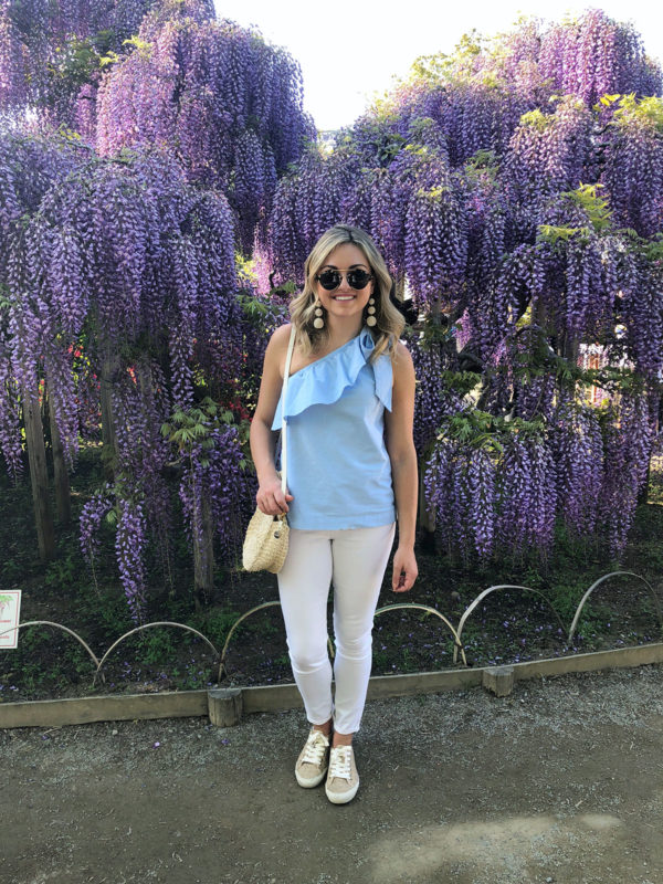 Bows & Sequins Travel Guide in Ashikaga Flower Park in Japan. Jessica Sturdy by purple wisteria flowers wearing a Vineyard Vines ruffled one-shoulder top, Old Navy white jeans, Seavees raffia sneakers, and a Clare V straw bag.