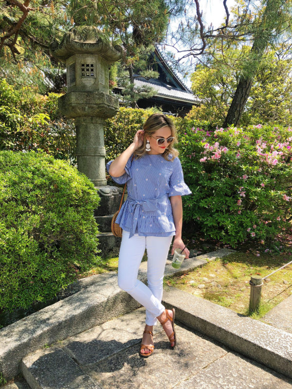 Jessica Sturdy in Kyoto Japan wearing a Nordstrom 1901 Striped Daisy Peplum Ruffle Top with White Jeans, Madewell leather sandals, white BaubleBar earrings, and a wicker bag from Bali.