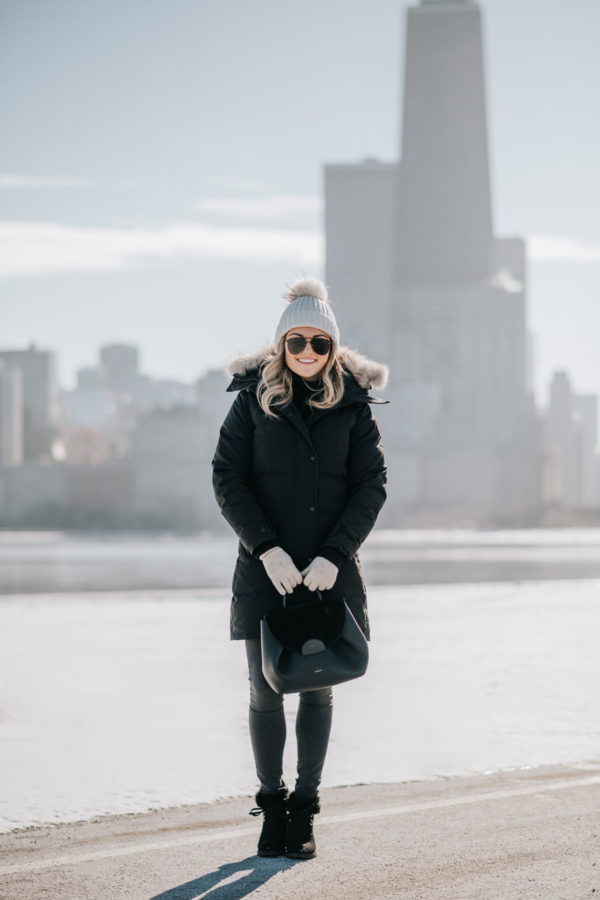 Jessica Sturdy wearing a fur-trimmed, hooded Canada Goose jacket with a pom beanie, matte aviators, booties, and a Polene top handle bag.