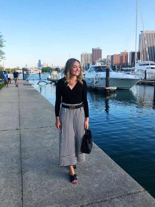 Jessica Sturdy wearing a black bodysuit, Gucci belt, black & white striped pants, and Kate Spade bow sandals by Belmont Harbor in Chicago.
