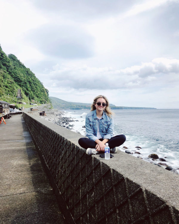 Jessica Sturdy in a travel outfit on the coast of Japan on the Izu Peninsula.