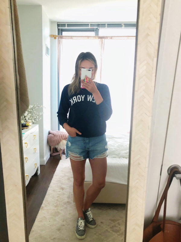 "Jessica Sturdy wearing a navy blue J.Crew ""New York"" sweatshirt, Cotton On denim cut off shorts, and Claudie Pierlot gingham sneakers for a casual weekend outfit."