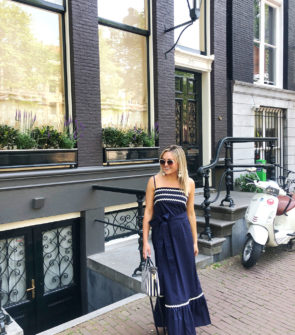 Jessica Sturdy wearing a Vineyard Vines navy blue ric rac maxi dress in front of a greystone on the canals of Amsterdam.