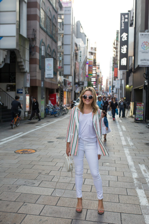 Jessica Sturdy wearing an all white outfit with a pink striped blazer in Osaka Japan.