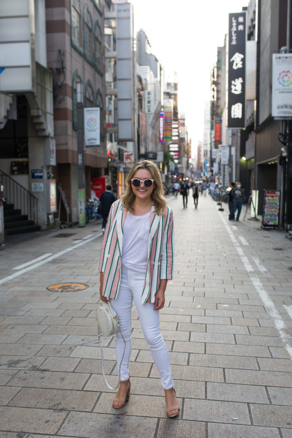 Fashion blogger Jessica Sturdy wearing a pink and white striped blazer with white jeans in Osaka, Japan.