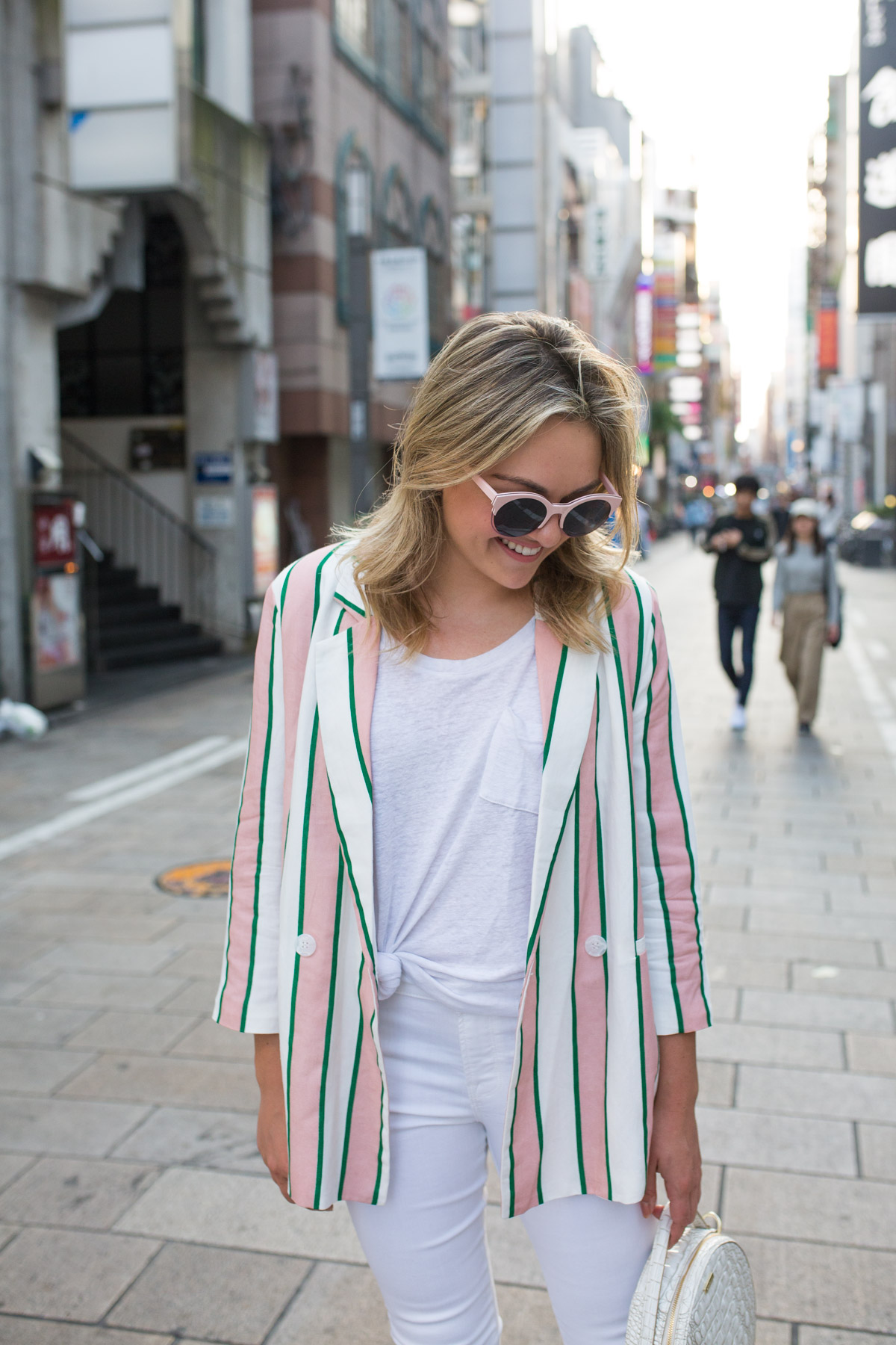 Travel Blogger Jessica Sturdy styling a pink and white oversized blazer with a knotted white tee and white jeans.