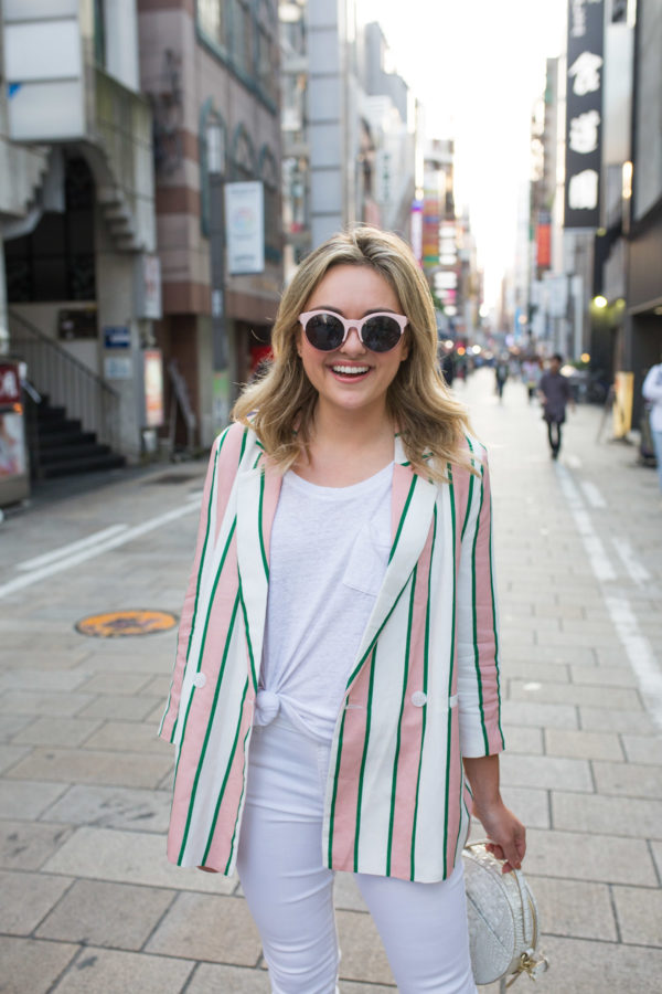 Travel blogger Jessica Sturdy wearing a striped blazer in Japan with pink sunglasses.