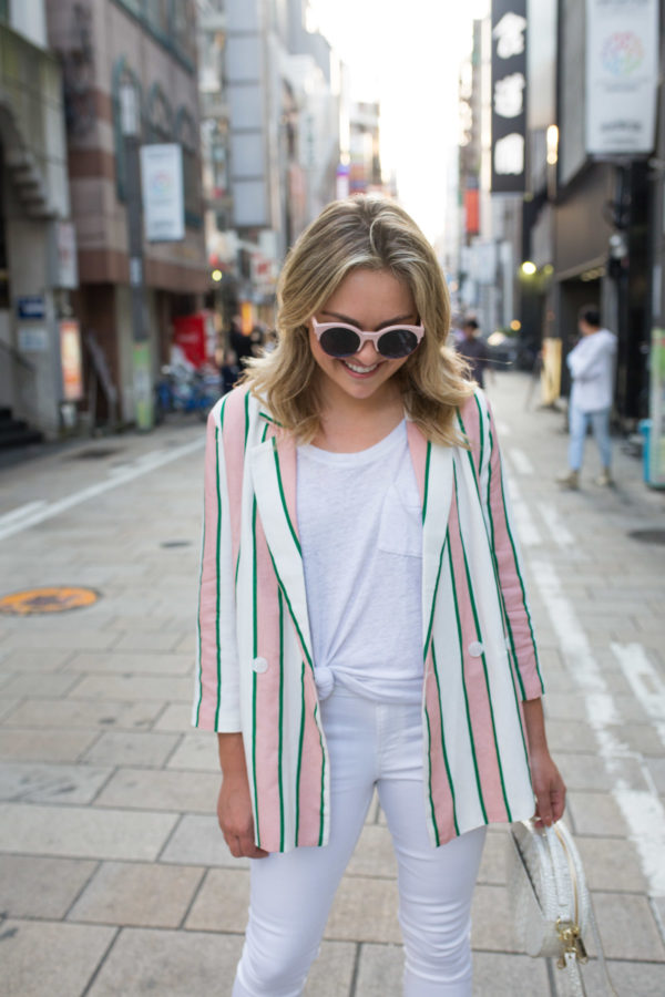 Lifestyle blogger Jessica Sturdy wearing a pink and white striped blazer with a white tee and white jeans in Japan.