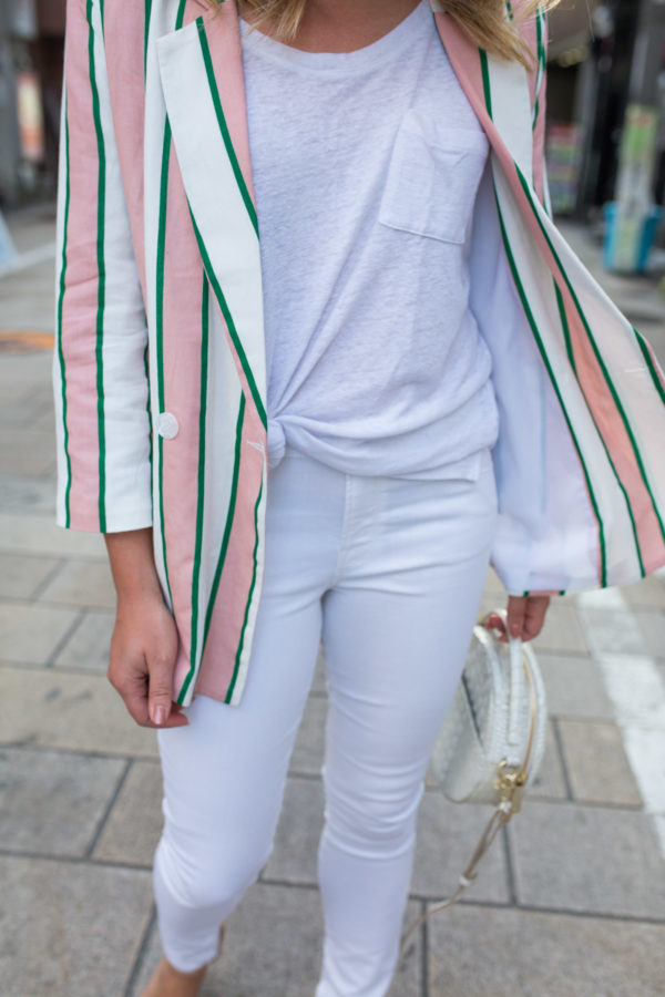 Fashion blogger Jessica Sturdy styling a white tee and white jeans with an oversized pink and white striped blazer in Osaka, Japan.