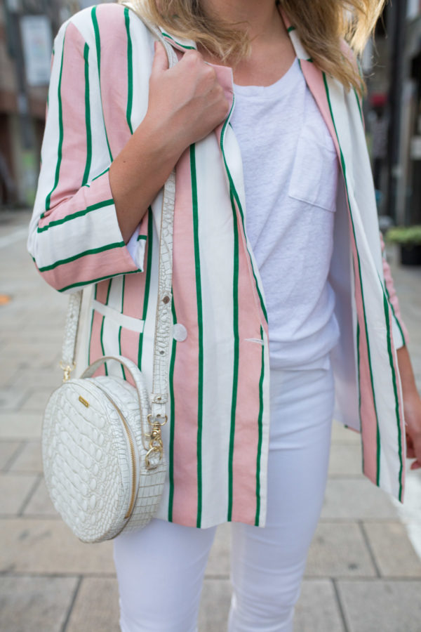 Jessica Sturdy styling a pink, white, and green oversized striped blazer with a round Brahmin handbag.