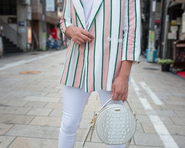 Jessica Sturdy styling an oversized striped blazer with white jeans and a round white bag.