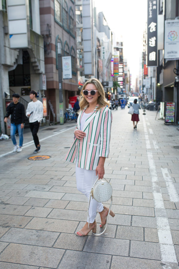 Fashion blogger Jessica Sturdy wearing a monochromatic white outfit with a striped blazer in Osaka, Japan.