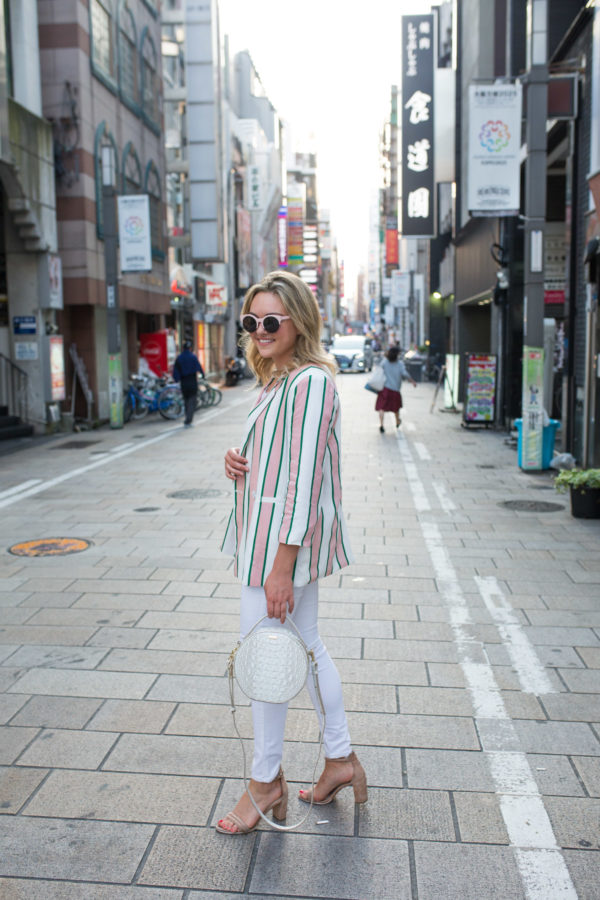 Fashion blogger Jessica Sturdy wearing an oversized blazer with white jeans, pink sunglasses, and a round bag in Osaka, Japan.