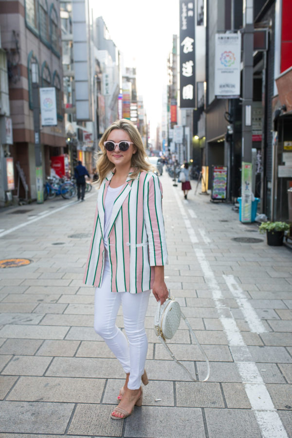 Fashion blogger Jessica Sturdy styling white jeans with a striped blazer, pink sunglasses, and white Brahmin bag in Osaka, Japan.