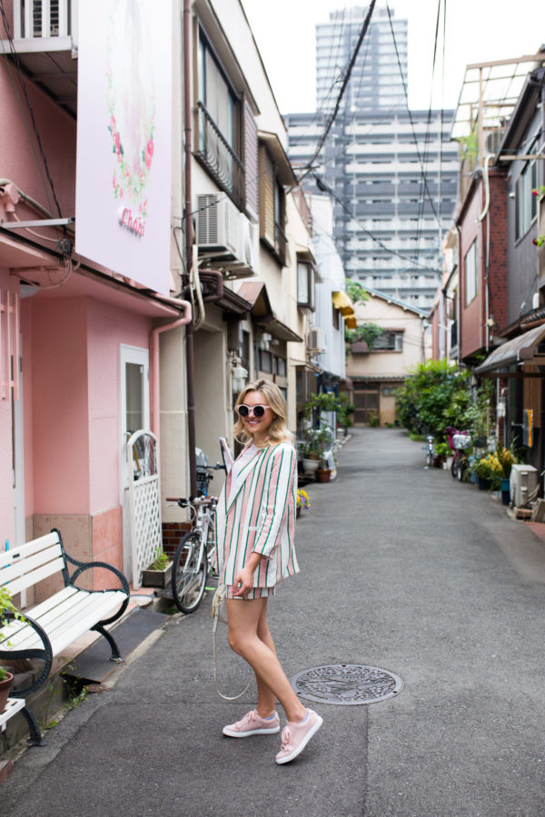 Jessica Sturdy wearing a pink and white striped short suit set in Japan with pink sneakers, pink sunglasses, and a round white bag.