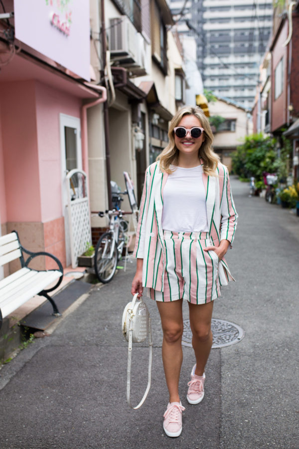 Jessia Sturdy wearing a pink, green, and white striped blazer with matching shorts and pink sneakers in Japan.