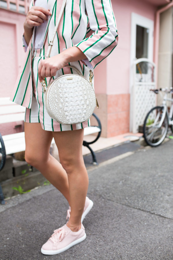 Travel blogger Jessica Sturdy wearing a matching blazer and short set in Japan with pink sneakers and a round white bag.