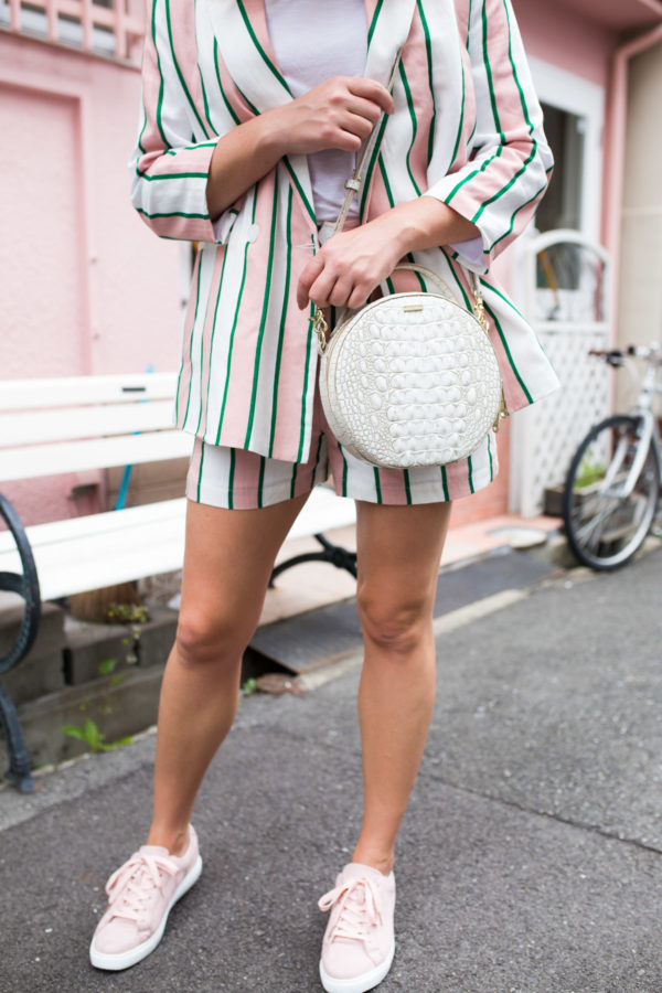 Lifestyle blogger Jessica Sturdy wearing a pink and white striped blazer with matching shorts, pink sneakers, and a white Brahmin bag.