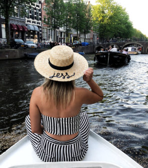 Jessica Sturdy wearing a black and white striped Lovers + Friends crop top and pants set with a monogramed straw hat that says Jess on the front of a boat in the scenic canals of Amsterdam.