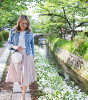 Jessica Sturdy on Philosopher's Path in Kyoto, Japan wearing a denim jacket and pleated pink midi skirt.