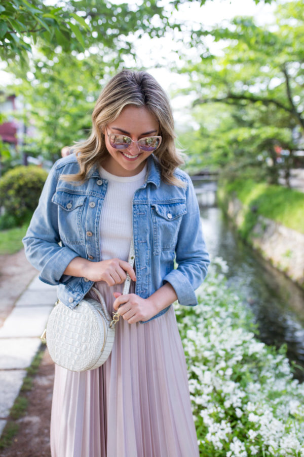 Chicago travel-based blogger and influencer Jessica Sturdy styling a denim jacket with a tee, pleated skirt, and round handbag in Kyoto, Japan along the Philosopher's Path walkway.