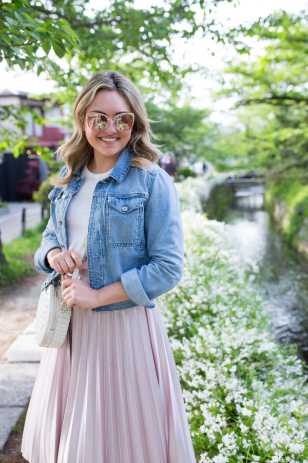 Chicago-based fashion influencer Jessica Sturdy wearing a denim jacket and rose gold sunglasses along the Philosopher's Path in Kyoto, Japan.