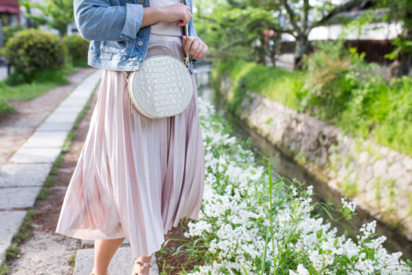 Jessica Sturdy carrying the new Brahmin Lane round handbag and a pleated pink midi skirt on Philosopher's Path in Kyoto, Japan.