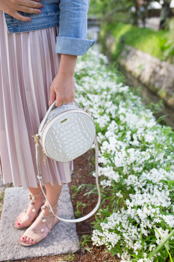 Jessica Sturdy on Philosopher's Path in Kyoto, Japan wearing a pleated skirt and a round white Brahmin handbag.