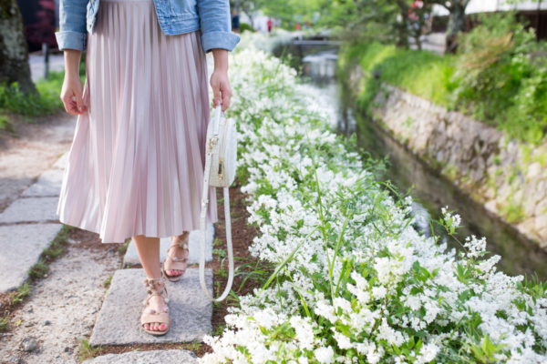 Jessica Sturdy wearing a pink pleated midi skirt and Loeffler Randall sandals on the Philosopher's Path in Kyoto, Japan.