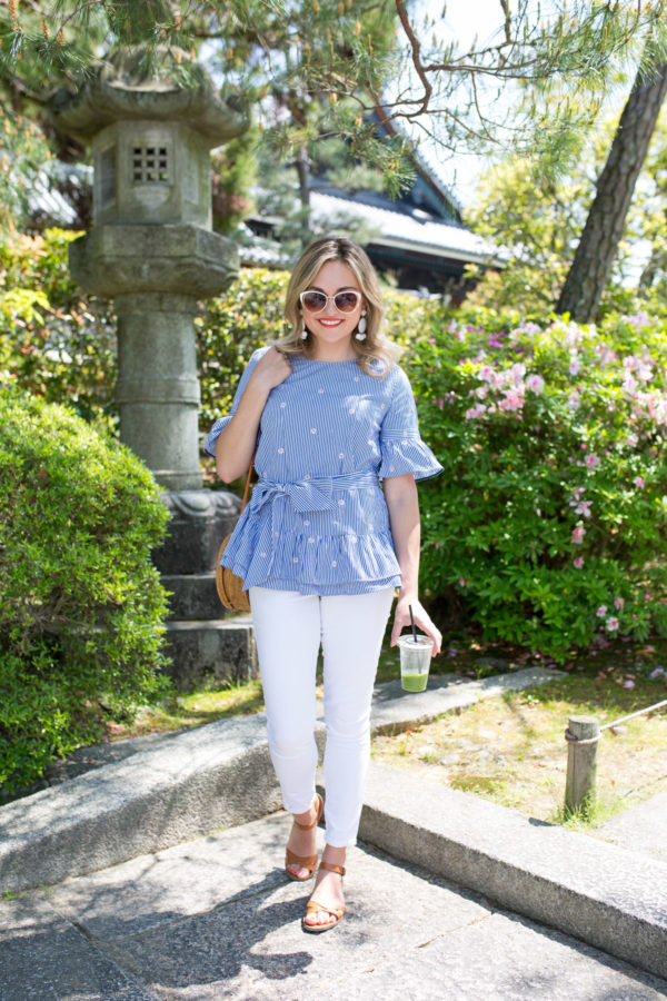 Jessica Sturdy styling a blue and white peplum top with white jeans and sandals in a garden in Kyoto, Japan.