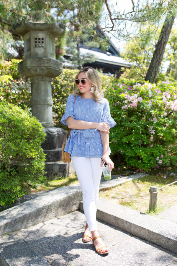 Jessica Sturdy styling a floral-printed striped peplum top and white jeans with leather Madewell sandals in a garden in Kyoto, Japan.