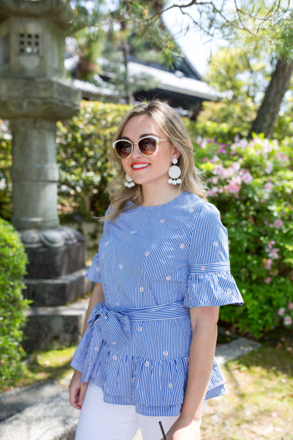 Jessica Sturdy wearing white BaubleBar earrings with a blue and white striped top with ruffled sleeves.