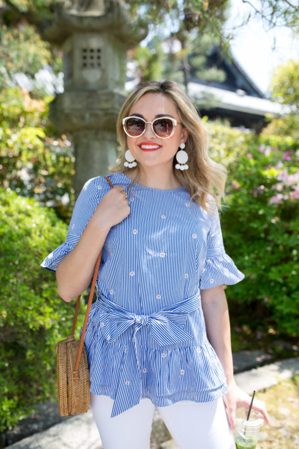 Chicago fashion blogger Jessica Sturdy styling a blue and white ruffled top with white sunglasses and statement earrings in Kyoto, Japan.