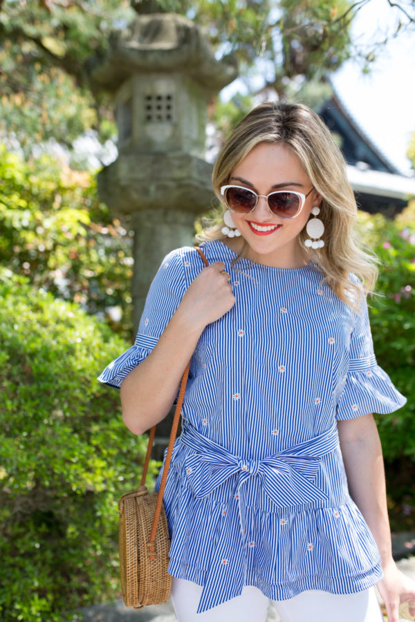Travel blogger Jessica Sturdy wearing a ruffled top and white accessories in a garden in Kyoto, Japan.