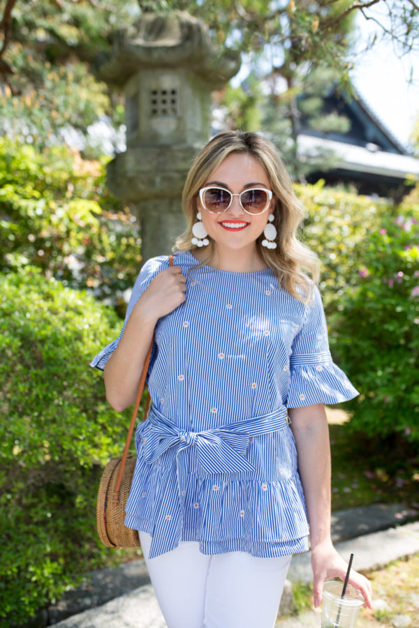 Jessica Sturdy wearing white BaubleBar earrings with a Nordstrom 1901 Daisy-Printed striped peplum top with white sunglasses in Kyoto, Japan.