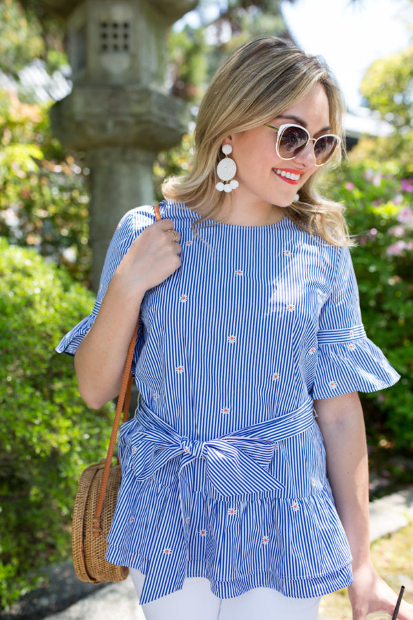 Style blogger Jessica Sturdy wearing a pair of white Baublebar statement earrings, white sunglasses, a bold lip, and a striped ruffle top with mini daisies.